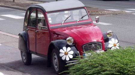 Voiture de collection « Citroën 2 Chevaux avec des stickers fleurs autour des clignotants »