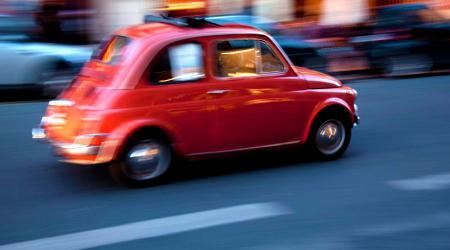 Voiture de collection « Fiat 500 rouge en pleine accélération »