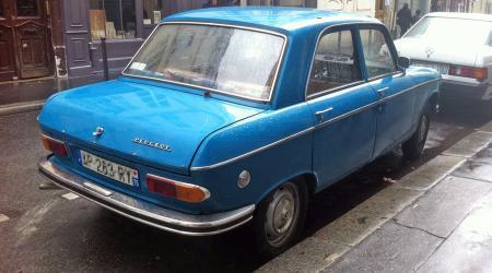 Voiture de collection « Peugeot 204 bleue sous la pluie vue de 3/4 arrière droit »
