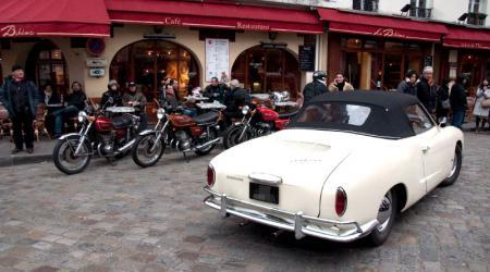 Voiture de collection « Volkswagen Karmann Ghia blanche vue de 3/4 arrière droit avec de vieilles motos en arrière plan »